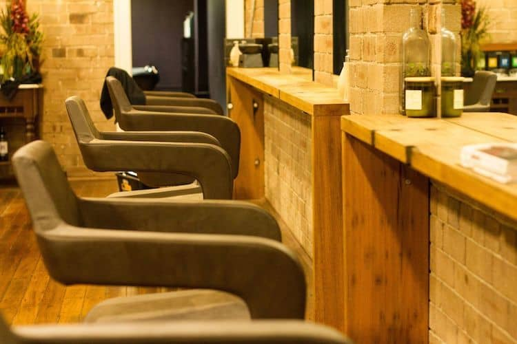 eclectic chairs and exposed brick complement the organic ethos of the salon